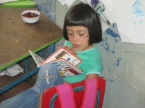A young girl reads to herself during a Bibliobus visit